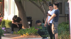 Young people playing Pokemon GO on main street Marham on cell phones Stock Footage