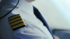Airline captain sitting in cockpit, adjusting uniform, getting ready for takeoff Stock Footage