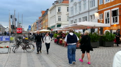 Tourists walking on cobblestones in Nyhavn along the canal - stock footage