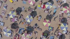 Aerial top view of crowded beach, people lounging under sun umbrellas Stock Footage