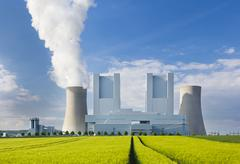 A shiny new lignite power station behind a rye field with wheel tracks leadin - stock photo