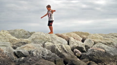 Child walks on the beach breakwaters Stock Footage