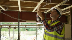 4K Construction worker on a building site checking roof struts & wiring Stock Footage