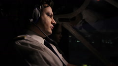 Night voyage over the city, attentive pilot steering airliner professionally Stock Footage
