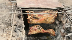 BBQ lamb hanging in ground cooking pit ready to eat HD Stock Footage