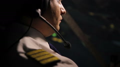 Attentive captain pilot in headset navigating huge airliner at night, job duties - stock footage