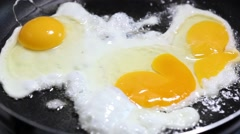 Scrambled from three raw eggs fried in a pan, close-up Stock Footage