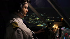Professional aircrew commander navigating airplane above city at night time Stock Footage