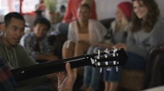 4K Happy group of friends hanging out at beach house, playing guitar & singing Stock Footage