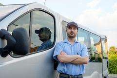 Portrait of confidence express courier next to his delivery van - stock photo