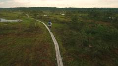 Aerial Shot of Man Walking through Swamp and Marsh Area. Stock Footage