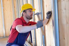 Carpenter using hammer in a construction site Kuvituskuvat