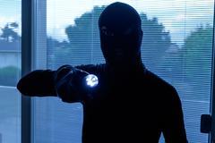 Burglar wearing a balaclava looking through the house window Stock Photos