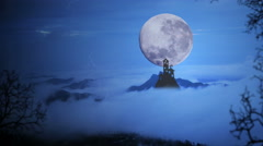 Dark castle with dramatic sky,fog, tree, full moon and clouds over mountain Stock Footage