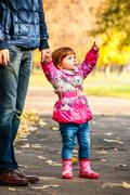 Little girl walks with my dad, pointing to something in the park Stock Photos