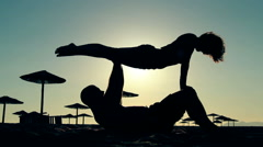 Acroyoga on the beach / Sunset silhouettes Stock Footage