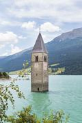 The old bell tower of Reschen in the reservoir Lake Reschen, Italy - stock photo
