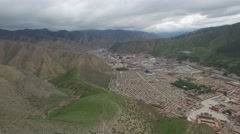 AERIAL L2R PAN SHOT OF XIAHE CITY AND TIBETIAN MOUNTAINS IN CHINA Stock Footage