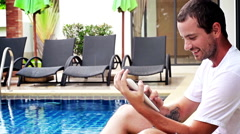 Young man with tablet sitting by the pool at the villa-3 - stock footage