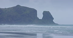 Ocean waves and cliff at Piha, Auckland, New Zeland Stock Footage
