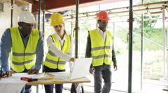 4K Architects with laptop at construction site & building crew working Stock Footage