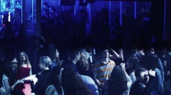 Crowd of dancing people on party in nightclub. Spotlights. Illuminations - stock footage