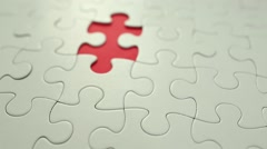 Hand places piece into puzzle Stock Footage
