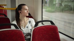 Pretty woman listening music in headphones on smartphone riding train Stock Footage