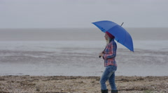 4K Cheerful young woman with colorful umbrella walking on beach on a gloomy day Stock Footage