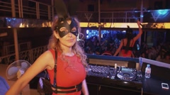 Dj girl in hare mask red dress dance on stage in nightclub. Look in camera Stock Footage