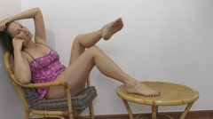 Pretty girl sitting on chair and massaging legs - full hd. Stock Footage