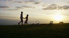 4K Silhouette couple walking at sunset Stock Footage