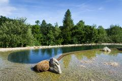 Natural swimming pond purifying water without chemicals through filters and p Stock Photos