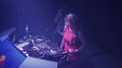Dj girl in red dress dance at turntable in nightclub. Mixing. Illuminations - stock footage