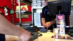 Customer buying Domino pizza and paying by credit card at check out counter Stock Footage