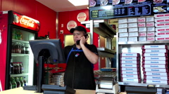 Worker taking phone call for customer ordering Domino pizza Stock Footage