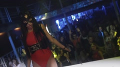 Mc girl in hare mask sexy red bodysuit dance on stage in crowded nightclub - stock footage