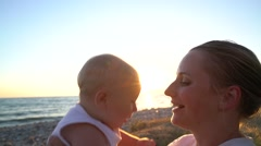 Mom coddling with a baby sitting on the beach at sunset - stock footage