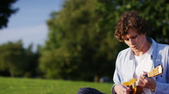 4K Attractive young man playing a ukulele Stock Footage