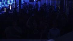 Happy dancing people on party in nightclub. Blue spotlights. Jumping. Strobe - stock footage