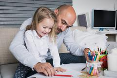 Father and daughter drawing together, creativity and learning concept - stock photo