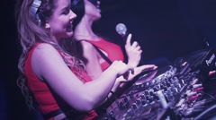 Mc girl and dj girl at turntable in nightclub. Dance. Mixing. Red dress. Smile Stock Footage