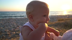 Mom coddling with a baby sitting on the beach at sunset Stock Footage