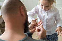 Father painting litttle daughters finger nails Stock Photos