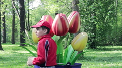 Boy Playing Near Giant Pot With Artificial Flowers Stock Footage