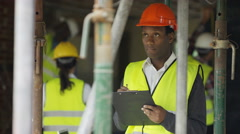 4K Portrait smiling worker at construction site writing notes on clipboard Stock Footage