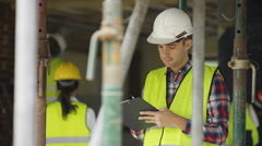 4K Portrait serious worker at construction site writing notes on clipboard Stock Footage