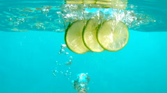 Three Lemon Slices Falling in Blue Water Bubbles Slow Motion Underwater Tabletop Stock Footage