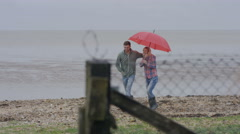 4K Cheerful young couple with red umbrella walking on the beach on a gloomy day Stock Footage