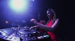 Mc girl in hare mask and dj girl in red dress mix at turntable in nightclub Stock Footage